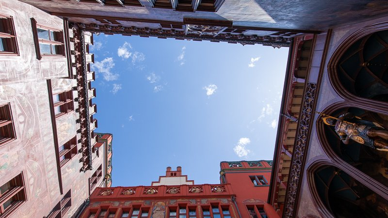 The inner courtyard gives you a 360° visual of the building's elaborate frescoes, eye-catching clock tower, and red façade.