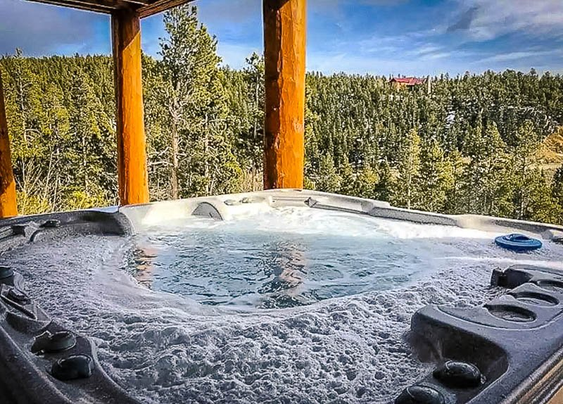 A hot tub on the deck overlooking the forest