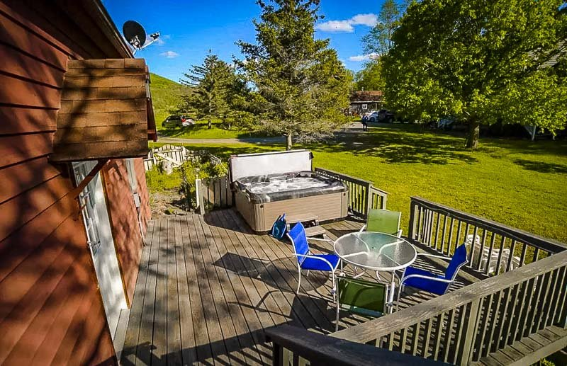 Wraparound deck with hot tub and deck furniture