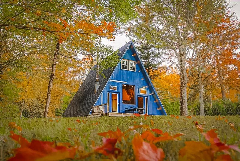 A-Frame cabin rental in the US surrounded by fall foliage.