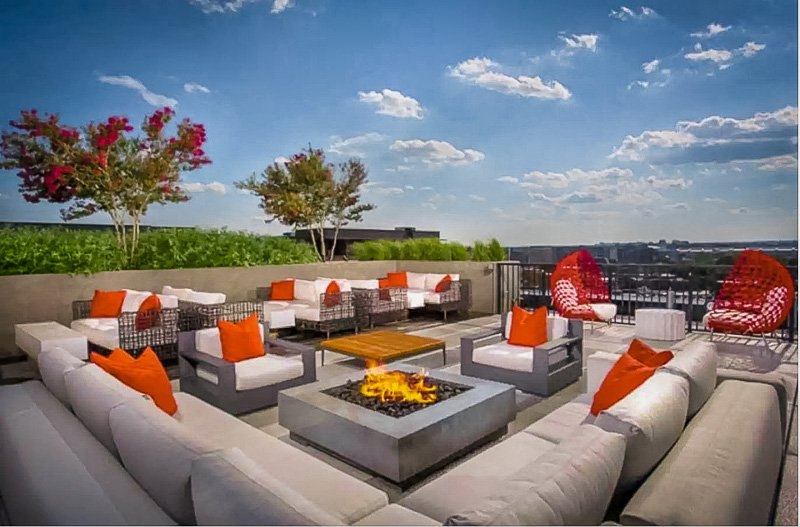 Expansive rooftop deck area with cozy furniture.