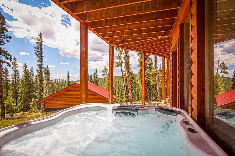 Oversized hot tub overlooking the surrounding forest and mountains.