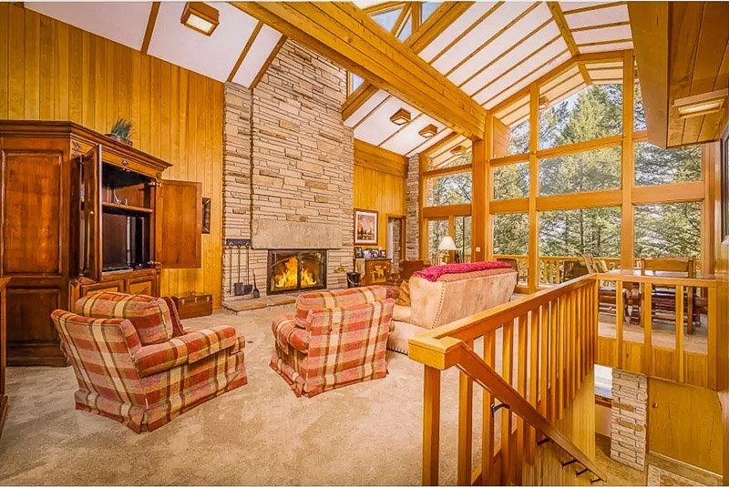 Cozy living room with indoor fireplace, rustic furniture, and beautiful views