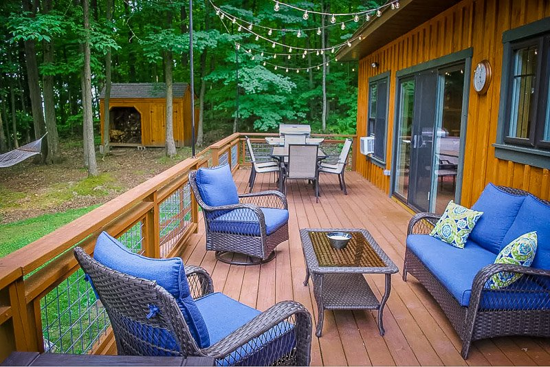Oversized back deck with outdoor furniture and a hammock.