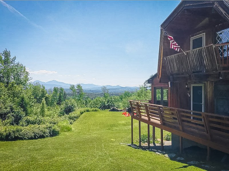 Expansive side porch with views of the backyard and mountains.
