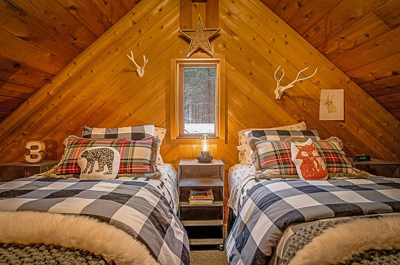 Cozy bedroom with rustic log cabin decor.