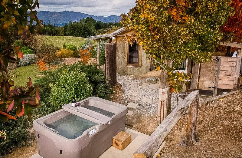 Cabin with an outdoor hot tub overlooking the lush New Zealand countryside