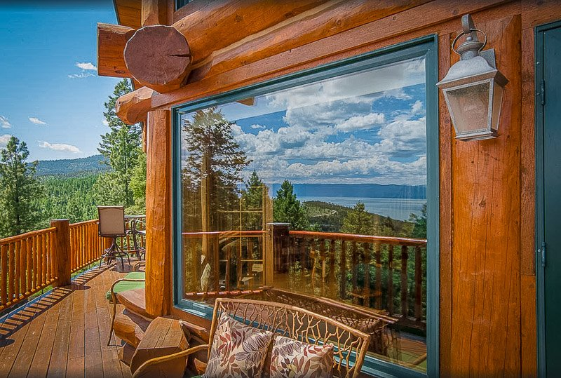 Wraparound porch at this MT cabin rental on a lake