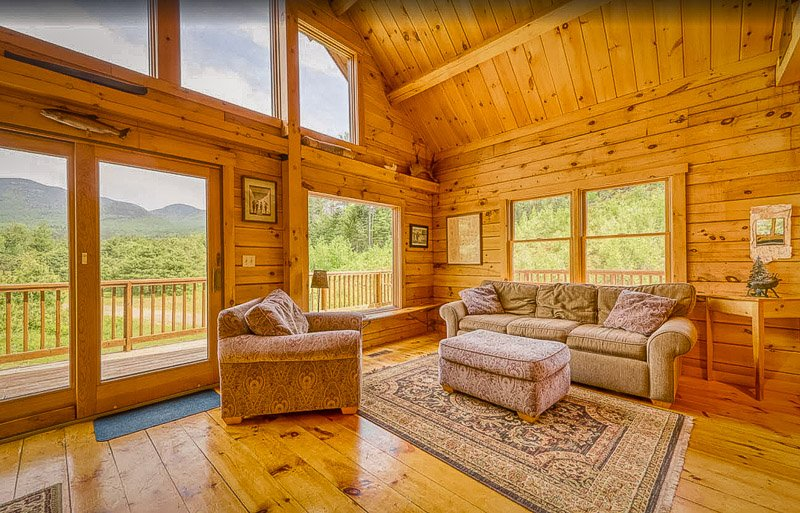 This log cabin for rent in New Hampshire offers unparalleled views of the mountains