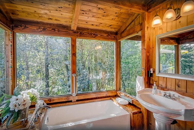 Bath tub with a view of the Hawaiian jungle.