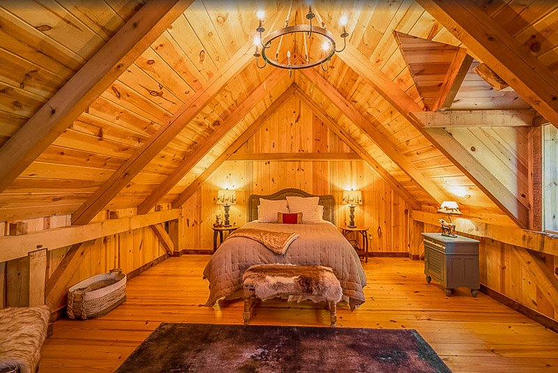 Master bedroom surrounded by rustic log cabin decor.