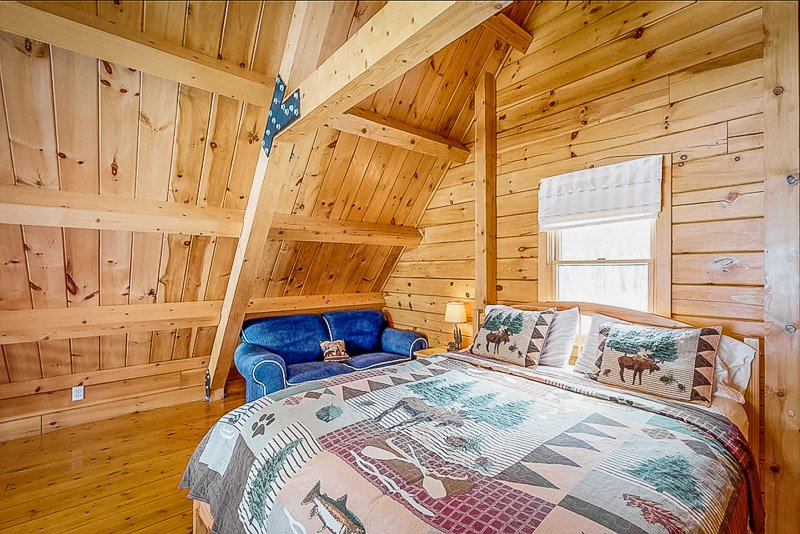 Bedroom inside this spacious lake house in ME